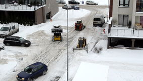 Cars pass tractor clean flat house parking lot winter snow stock video