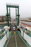 Cars and passengers disembark from Japanese ferry. Kure, Japan - November 13, 2010: Cars and passengers disembark from a ferry at Kure port in Japan assisted by Stock Photos