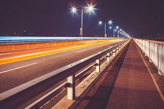 Cars passing bridge through Han river and leaving lights traces behind them - Seoul, South Korea. Several cars passing bridge through Han river and leaving Stock Images