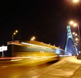 Cars are passing by the night bridge. Cars pass through the night bridge. Night city in the headlights royalty free stock images
