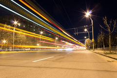 Light streaks of cars passing by in the night. Light streaks of cars and public transport leaving light trails in Bucharest Royalty Free Stock Image
