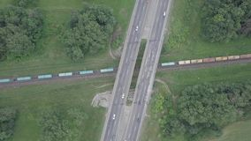 Overpass over railway. Cars passing over the bridge over the trains stock footage