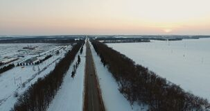 Cars passing through the winter asphalt road. Aerial view. Aerial shot of cars and trucks driving on a road on winter evening. The road goes into the horizon stock video