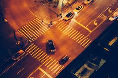 Cars and people on road intersection with signal lights and crosswalks at night time in the city street. Royalty Free Stock Photo