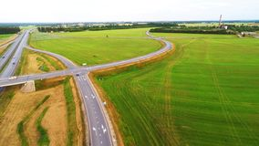 Cars quickly go on the high-speed route. Aerial footage. Aerial footage of green fields and high speed road stock footage