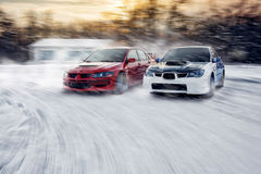 two cars fast drive race speed at winter impreza and lancer evolution royalty free stock images