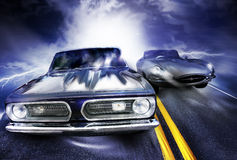 Cars racing. Two fast vintage cars racing from a bright light with lightening flashes down the side of the road Royalty Free Stock Image