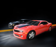 Cars racing. Two Chevrolet autos (Camaros) race down a dark highway Stock Photo