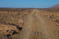 Cars resurfacing tracks in the stony desert, Morocco Stock Photos