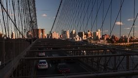 Cars riding and pedestrians walk over the Brooklyn Bridge at sunset stock video
