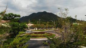 Cars riding on roundabout in small town near jungle. Vehicles riding on circular intersection of main road in middle of. Small town against mountain and jungle stock footage