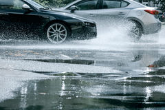 Cars riding through water puddles on road after rain Royalty Free Stock Photo