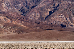 Cars on Road in Death Valley. Afternoon sun lights up the red and brown earthy desert tones in Death Valley National Park California. Cars are driving beneath Royalty Free Stock Photos