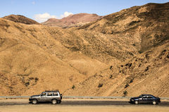 Cars on a road in desert mountains Royalty Free Stock Images
