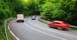 Cars on road in forest Stock Photos