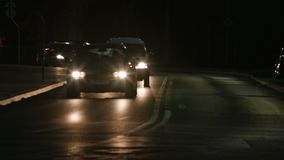 Cars on the Road at Night. Cars with their lights on on the road at night. Long shot stock footage