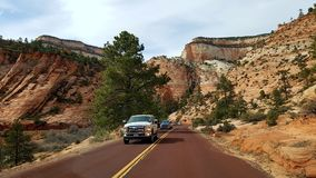 Cars on roadway through Zion Canyon, Utah. Cars on road through Zion Canyon in rural Utah, USA on sunny day stock photo