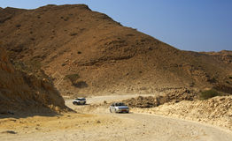 Cars on a rocky rough road in a wadi Royalty Free Stock Photos