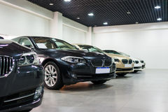 Cars for sale in showroom. Lined up cars in dealership showroom for sale Stock Photography