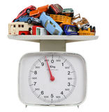Cars on a scale. Pile of cars on a kitchen scale isolated on white with clipping path Royalty Free Stock Image