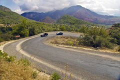 Cars on serpentine road in mountains. Two cars go up the serpentine road in mountains in cloudy weather Royalty Free Stock Photos