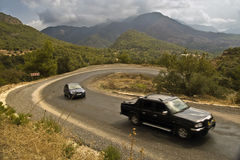 Cars on serpentine road in mountains. Two cars go up the serpentine road in mountains in cloudy weather Stock Photography