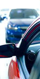 Cars in showroom. Red and blue cars in showroom, with blue car in background blurry Stock Image