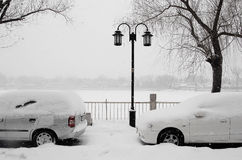 Cars in snow beside lake. Cars parked at the bank of lake under snow stock photo