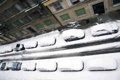 Cars snowed under. Cars covered by snow parked in a street Stock Photos