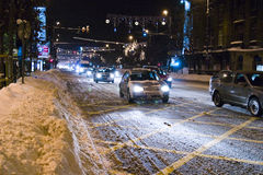 Cars on snowy road in Bucharest. Cars driving along Magheru Avenue, Bucharest with piles of snow on the pavement after heavy snowfall. Night shot Royalty Free Stock Images