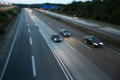 Cars speeding on a highway in the evening. Some cars speeding on a highway in the evening Stock Photos