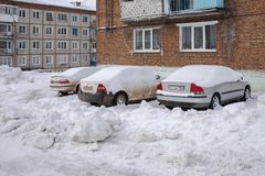 Cars stand, covered with snow, next to the house. Severe climate in the village of Belogorsk, Tisulsky district, Kemerovo region. Siberia. Russia Royalty Free Stock Photo