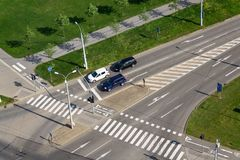 Cars standing in front of crosswalk on crossroad, aerial view. Aerial view of cars waiting in front of crosswalk and bike crossing line on crossroad, driverless royalty free stock images