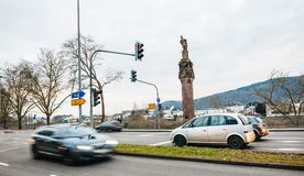 Cars and statue of Emperor Constantine holding a crown. TRIER, GERMANY - FEB 21, 2015: Row of cars and statue of Emperor Constantine holding a crown with a cross Royalty Free Stock Photos