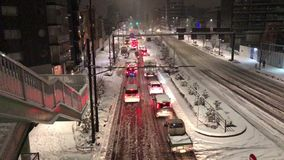 Cars stuck in Tokyo as pedestrians and traffic struggle during a rare snow storm.