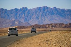 Cars with tourists travel among the stunning landscapes of the Namib Desert, surrounded by mountains royalty free stock photos