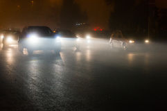 Cars in traffic at night. Headlights and taillights of cars driving on roadway in traffic at night in fog Royalty Free Stock Photos