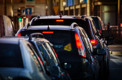 Cars is in traffic in the street. A group of cars is in traffic in the street in the evening. View from the back Royalty Free Stock Image
