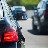 Cars in traffic. Tail light of a driving car with blurred car traffic in the background royalty free stock photos