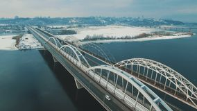 Cars and train moves on a bridge over a frozen river aerial drone footage. 4K stock video footage