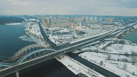 Cars and train moves on a bridge over a frozen river aerial drone footage. 4K stock footage