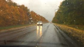Cars travel go on the road asphalt. autumn beautiful view forest, raindrops on the glass car blurred background slow. Cars travel go on the road asphalt. autumn stock footage