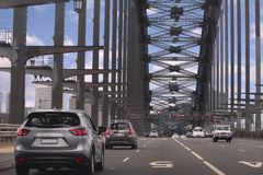 Road across the Sydney Harbour Bridge. Cars travelling across lanes of the Sydney Harbour Bridge under the the arch Royalty Free Stock Photos