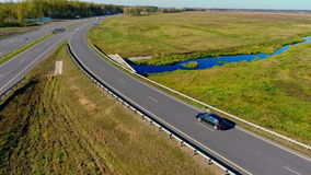 Cars and truck moving on road junction. Drone view of highway road. Sky view of cars traffic at highway road in field. Aerial view cars driving on highway stock footage