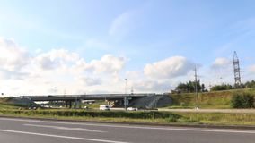 Cars, trucks move on road and under overpass. At summer day stock video footage