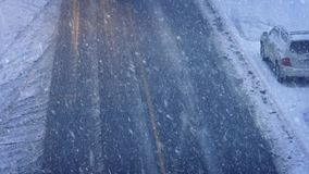 Cars And Trucks Passing In Blizzard. High-angle shot of vehicles passing on road in snowstorm stock video
