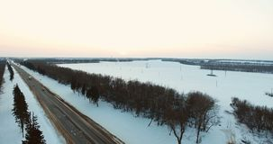 Aerial view of trucks and cars moving on winter road. 4K. Cars and trucks rides by road at winter evening aerial view. The sun is setting. The road goes up into stock video