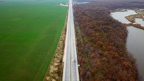 Cars and trucks running on the highway. Aerial images downward shot from the drones. Trucks and cars are moving on the highway at high speed. Images drawn along stock footage