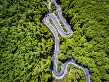 Cars and trucks on winding road trough the forest, Transilvania,. Romania Royalty Free Stock Photo