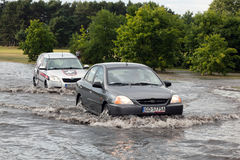 Cars trying to drive against flood on the street in Gdansk, Poland. Stock Images
